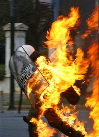 A GREEK RIOT POLICEMAN IS ENGULFED IN FLAMES FROM A PROTESTER'S PETRO BOMB ON DEC. 12, 2008 IN ATHENS