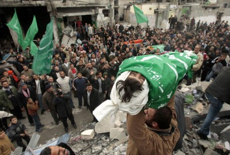 A RELATIVE CARRIES THE BODY OF EIGHT-YEAR-OLD DINA BALOUSHA DURING HER FUNERAL